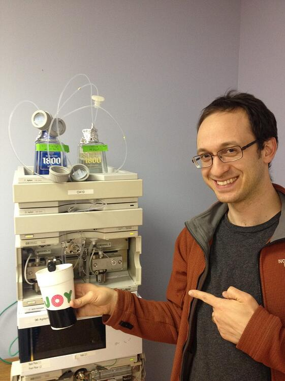 President and Founder Michael Kahn poses with MCR's first High-Performance Liquid Chromatography machine. Back before they could afford mobile phase bottles, they used tequila bottles in their place while experimenting with MCR's first cannabinoid method.